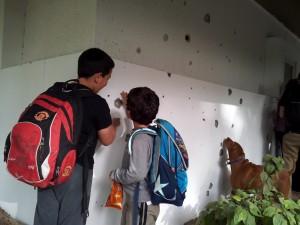 Schoolchildren, and a dog, at Kibbutz Nir Oz examine Kassam rocket damage to a kindergarten in  previous attack (Illustration, photo: Dave Bender)
