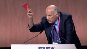 Palestinian soccer official Jibril Rajoub waives a symbolic red penalty card at Israel during the 65th FIFA Congress. Photo: YouTube.