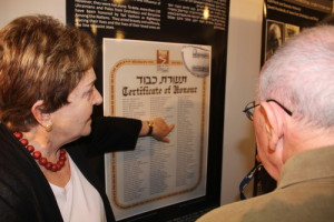 """Standing in front of a poster at the Tel Aviv's Beit Hatfutsot museum with a list of individuals who had saved Jews in Drohobych-Boryslav during the Holocaust, Irena Wysoki points to the names """"Jan Sawiński"""" and """"Zofia Sawińska,"""" Polish farmers who hid Wysoki and her brother. Photo: Eitan Arom."""